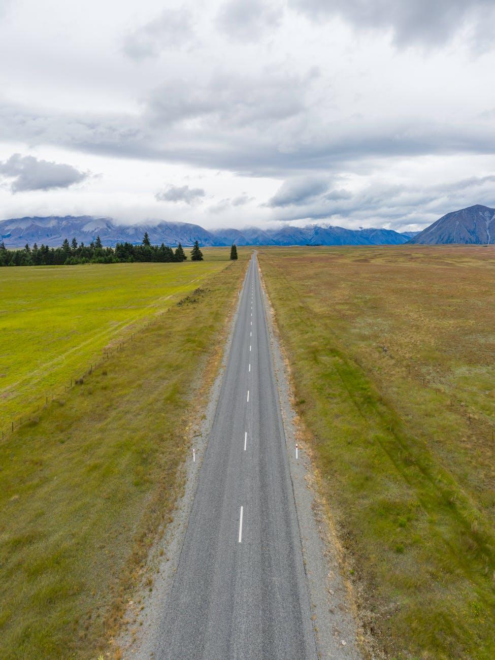 gray asphalt road between green grass field